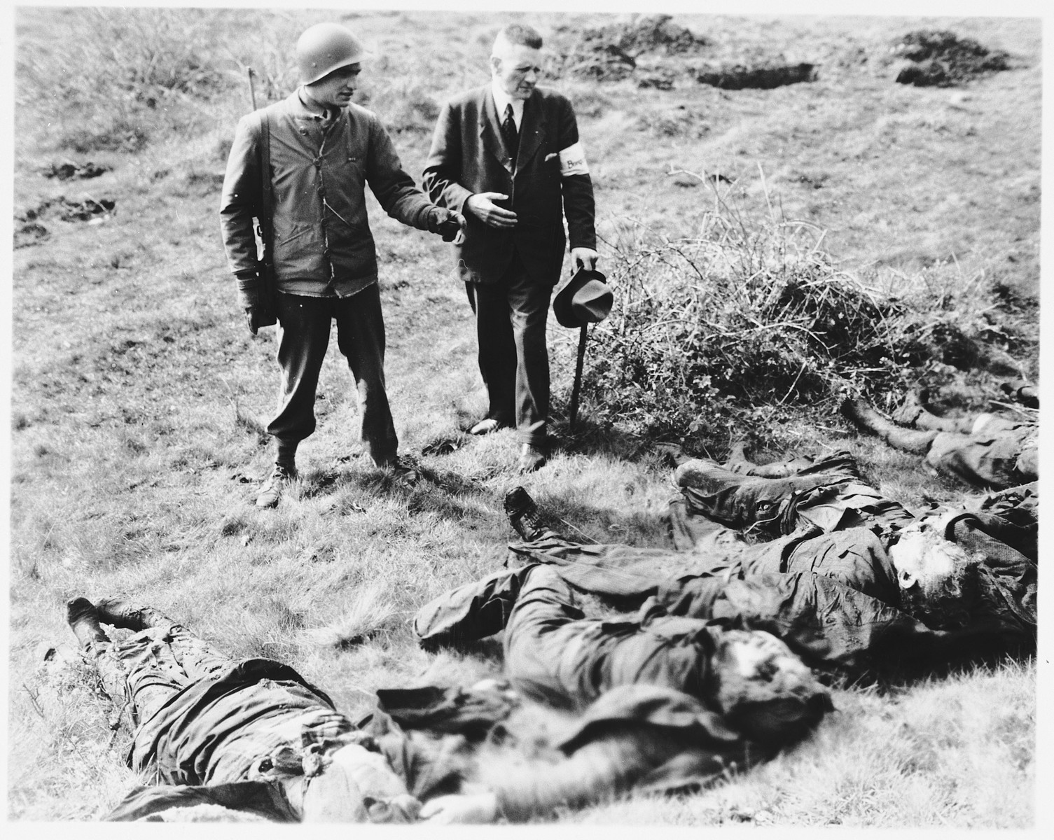 An American soldier and local civilian official examine corpses found near Warstein.  The victims were shot by German police prior to the arrival of U.S. troops.