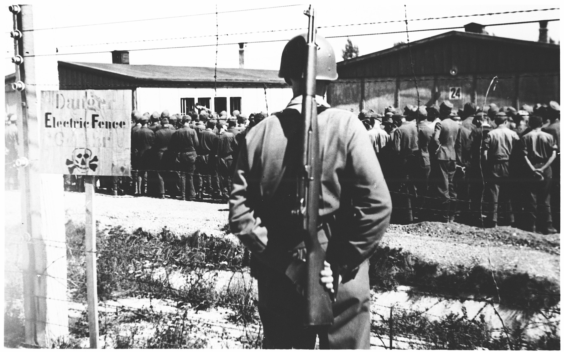 An American soldier stands guard over German POWs in Dachau.