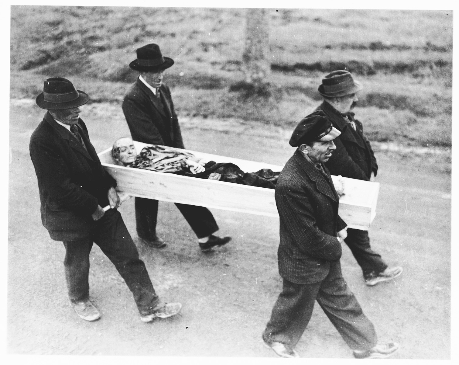 German civilians from Neunburg carry a body found in a nearby forest to the town cemetery for proper burial.   The victim was a Jewish prisoner from Flossenbuerg shot while on a death march.