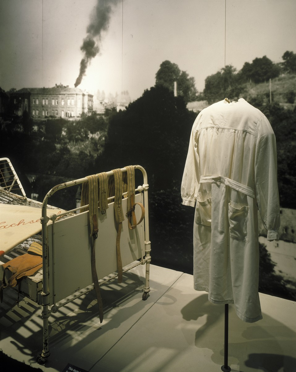 "Detail of the ""Murder of the Handicapped"" segment, featuring a bed, blanket and doctor's smock from the Sachsenberg clinic, on the fourth floor of the permanent exhibition in the U.S. Holocaust Memorial Museum."
