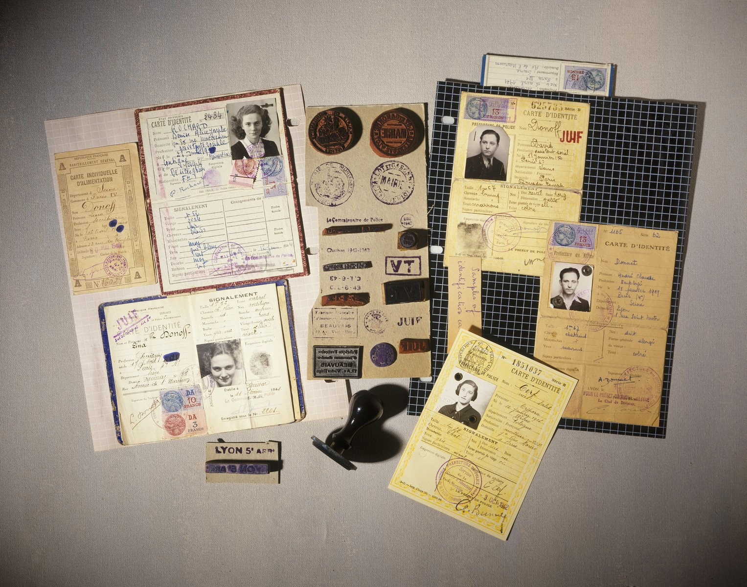 Collage of forged French identification papers and the rubber stamps used to produced them, displayed on the second floor of the permanent exhibition at the U.S. Holocaust Memorial Museum.  Among the collection are:  1. (Frank, 1988.077): Forged identification papers and rubber stamps.  2. (Cerf, 1991.070): Forged identification papers and rubber stamps.