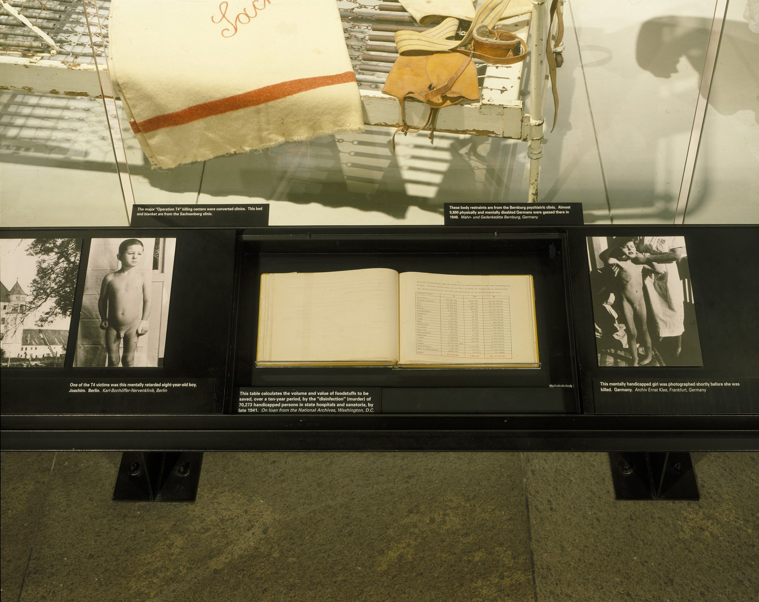 "Detail of the ""Murder of the Handicapped"" segment, featuring the Hartheim Institute register and photographs of euthanasia victims, on the fourth floor of the permanent exhibition in the U.S. Holocaust Memorial Museum."