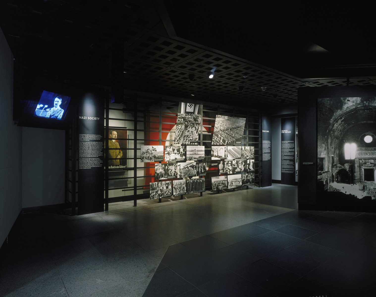 "View of the ""Nazi Society"" segment in the U.S. Holocaust Memorial Museum permanent exhibition.  The segment uses photographs, film, artifacts and text to describe the Nazification of German society. The display includes a Nazi banner that once flew over Hitler's mountain retreat near Berchtesgaden in Bavaria.  In 1920, at Hitler's urging, the Nazi party adopted the swastika as its official symbol. A law passed on September 15, 1935 declared the Nazi banner to be the national flag of Germany."