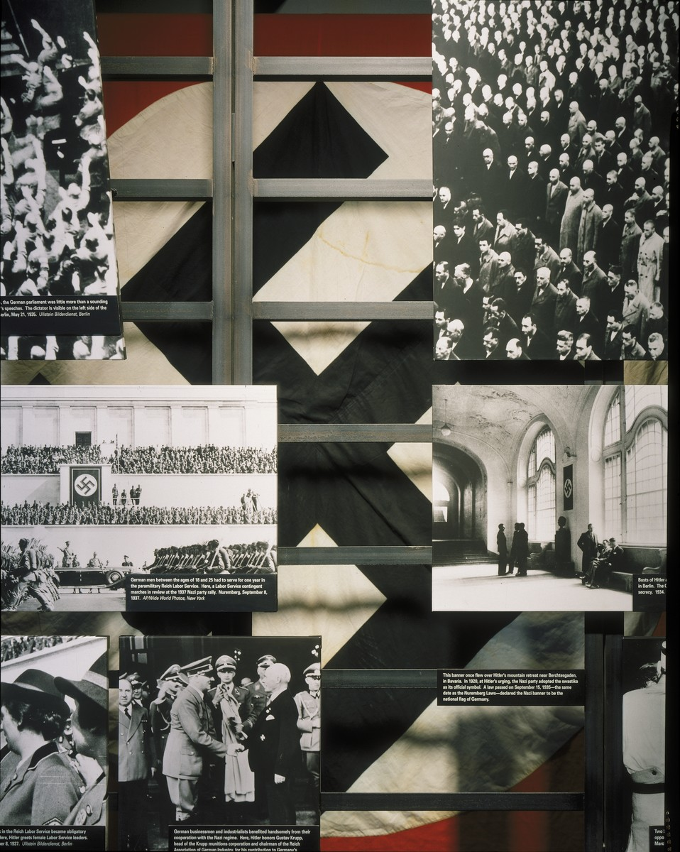 "Detail of the ""Nazi Society"" segment in the U.S. Holocaust Memorial Museum permanent exhibition.  The segment uses photographs, film, artifacts and text to describe the Nazification of German society. The display includes a Nazi banner that once flew over Hitler's mountain retreat near Berchtesgaden in Bavaria.  In 1920, at Hitler's urging, the Nazi party adopted the swastika as its official symbol. A law passed on September 15, 1935 declared the Nazi banner to be the national flag of Germany."