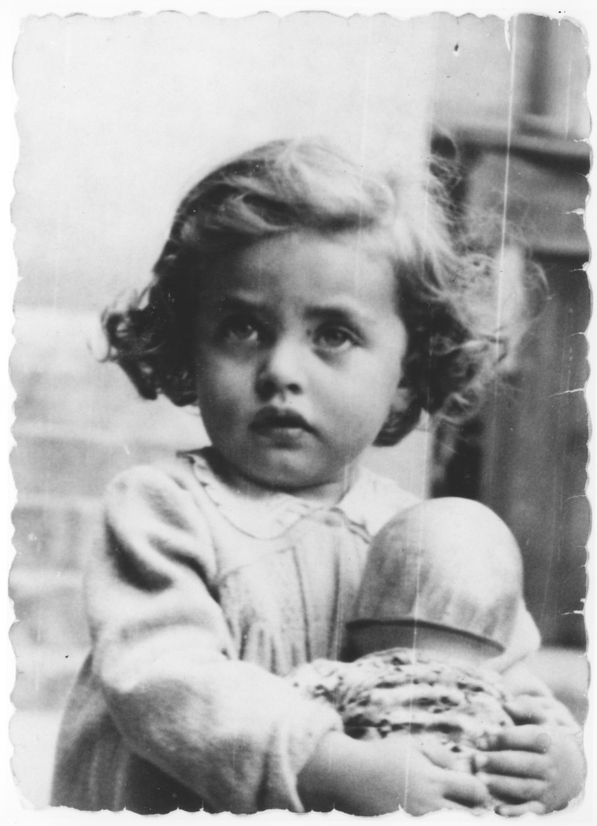 Portrait of Basia Israel clutching a doll in the Krakow ghetto.