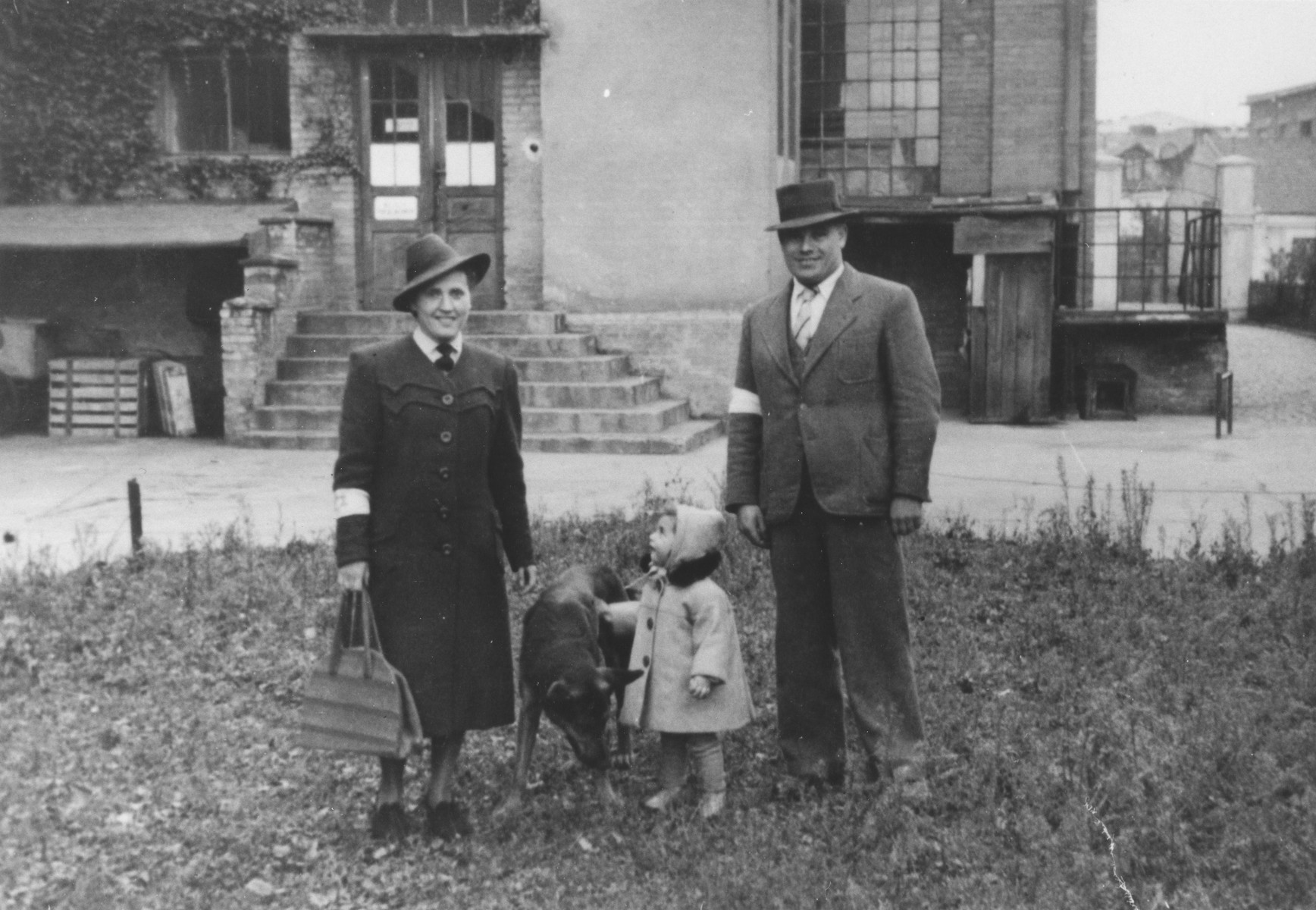 Basia Israel stands with her parents and a dog in the Krakow ghetto.