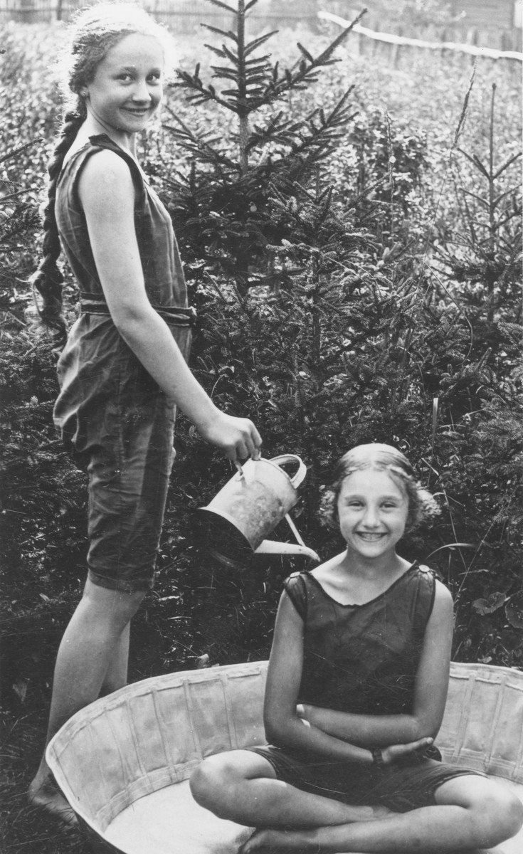 Irenka Huber pours water down the back of her sister Eliska with a watering can.