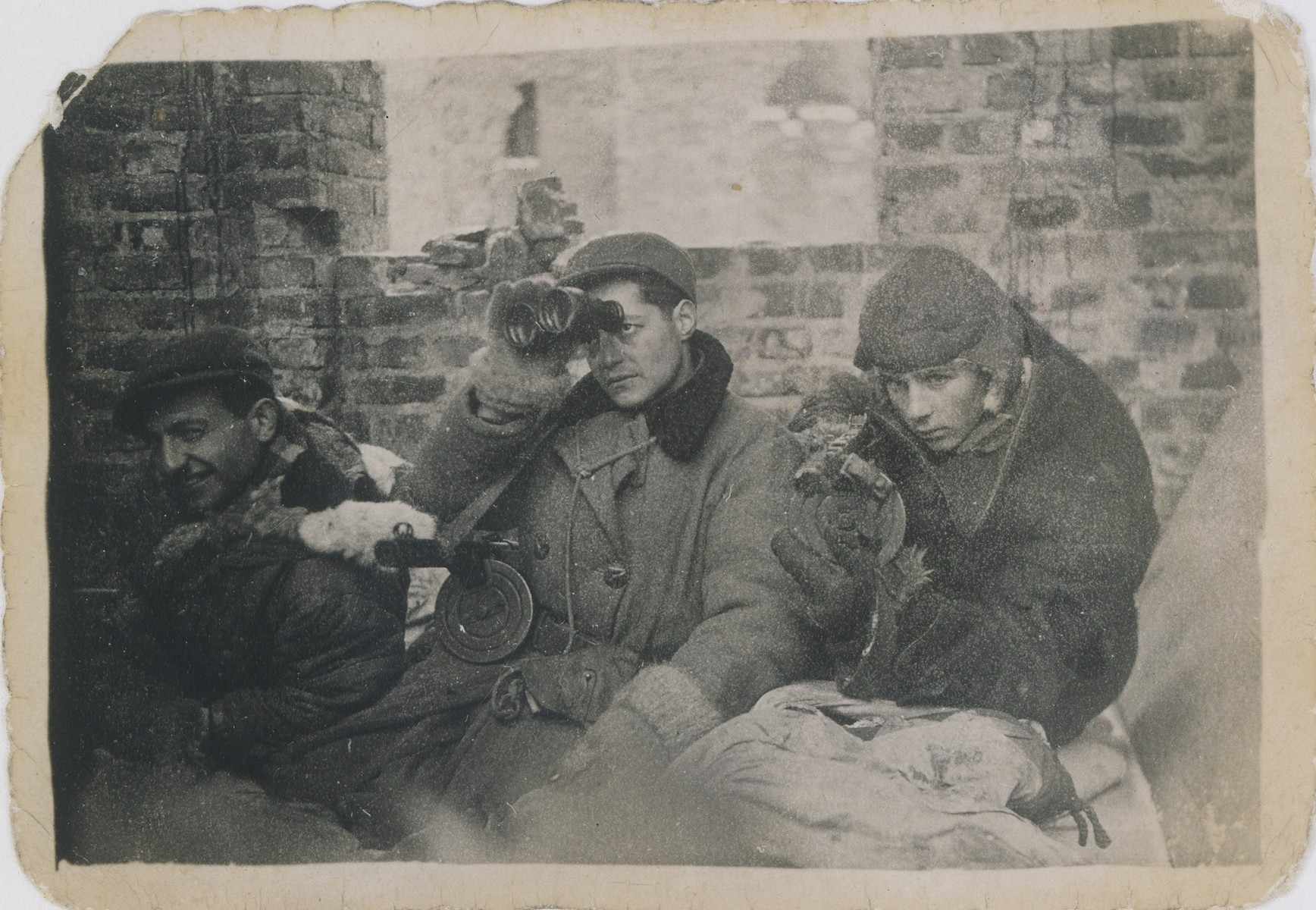 Jan Kostanski (right) crouches with Marek and Adas (right and center) in a bunker during the Warsaw uprising.