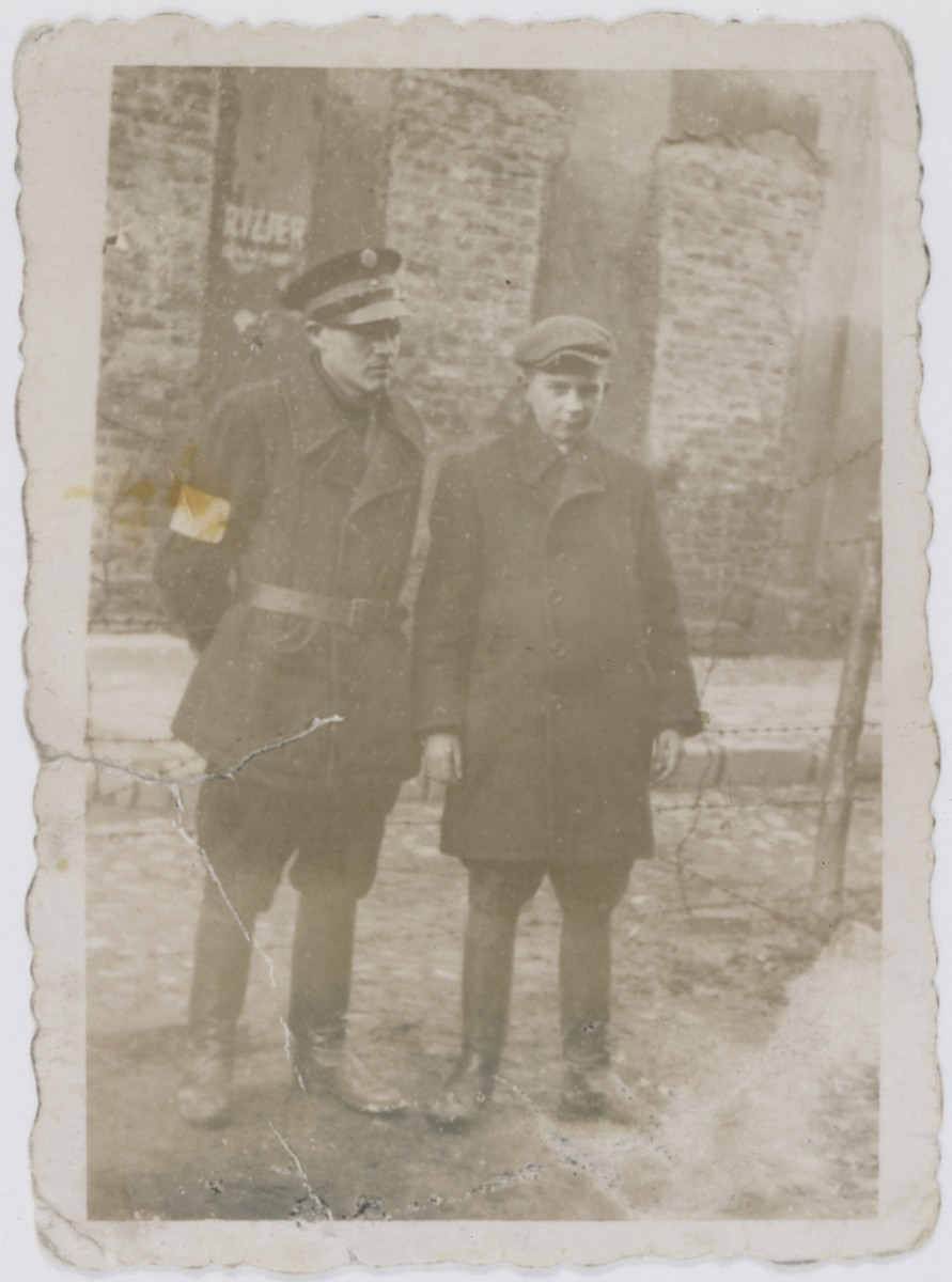 Jan Kostanski stands next to a Jewish policeman in front of a barbed wire fence on Krochmalna Street in the Warsaw ghetto.