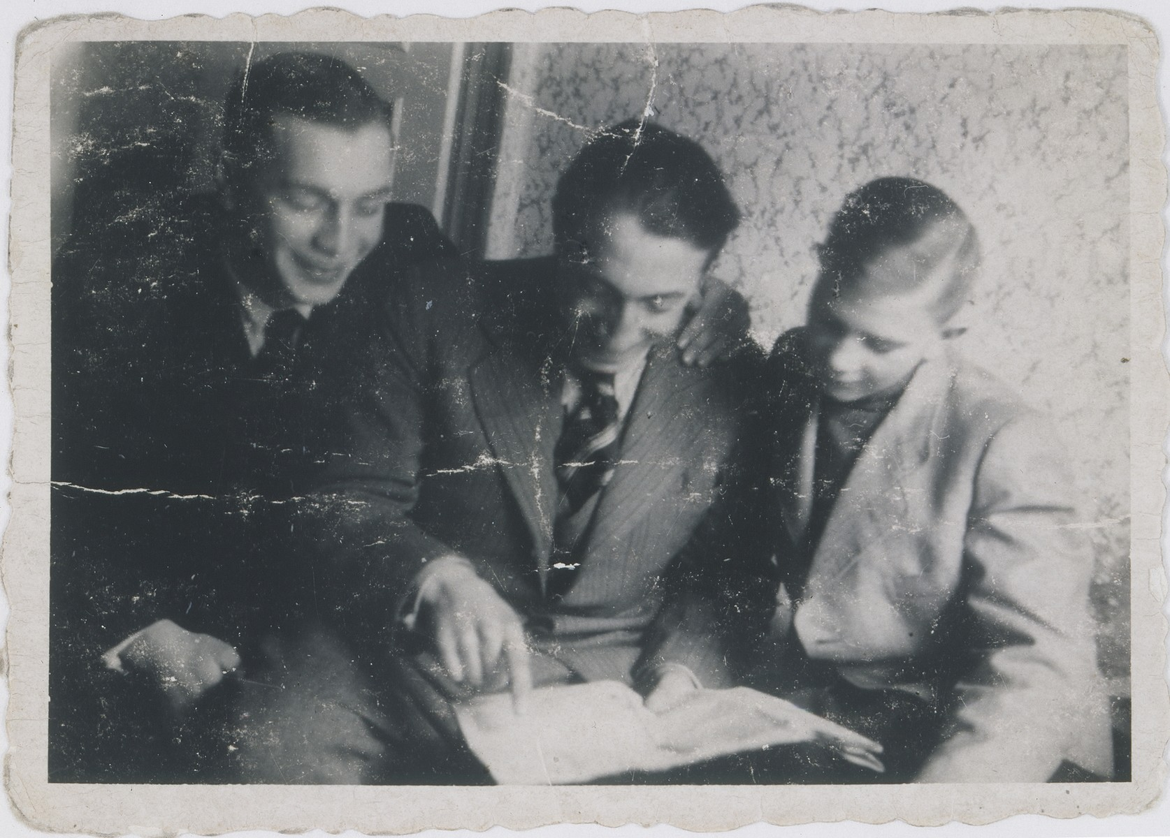 Jakob Wierzbicki (center) reads to Jan Kostanski (right) and Edek (left) in the Warsaw ghetto.