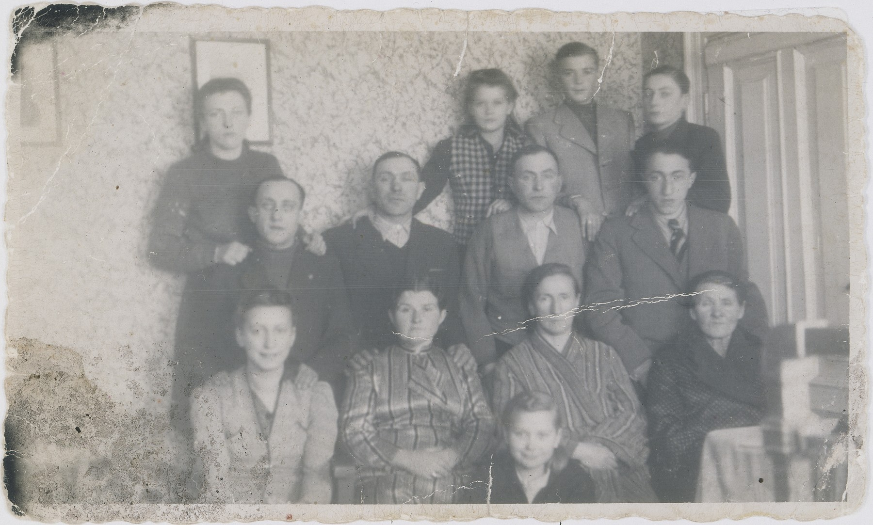 Portrait of the Wierzbicki and Kostanski families in the Warsaw ghetto.  Pictured in the center, front is Danusia.  In the front row from left to right are: Fela, Wladyslawa Wierzbicka, Berkowa, Grandma Bajla.  In the second row from the front, from left to right are: Szmulek, Ajzyk, Berek, Jakob.  In the top row from left to right are: Nacha, Jadzia, Jan and Nathan.