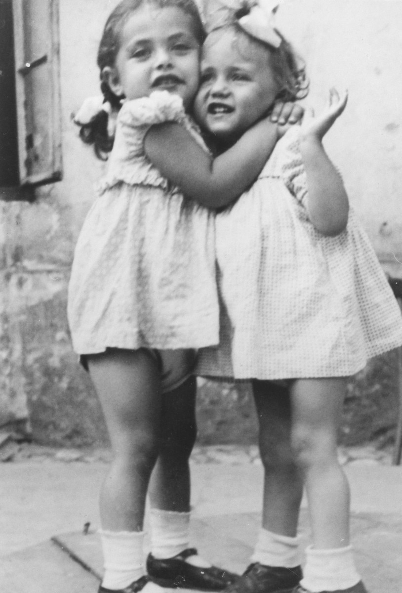 Close-up portrait of three-year-old Basia Israel hugging another young girl in the Krakow ghetto.