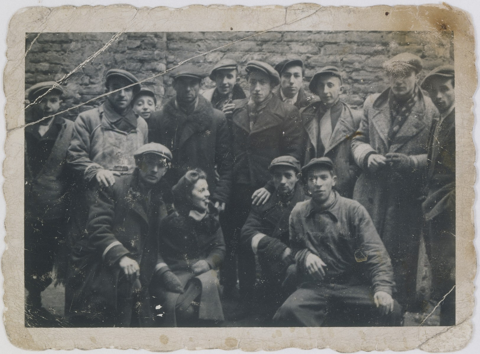 Group portrait of Jewish youth involved in smuggling goods into the Warsaw ghetto in a courtyard located at Plac Mirowski 9.