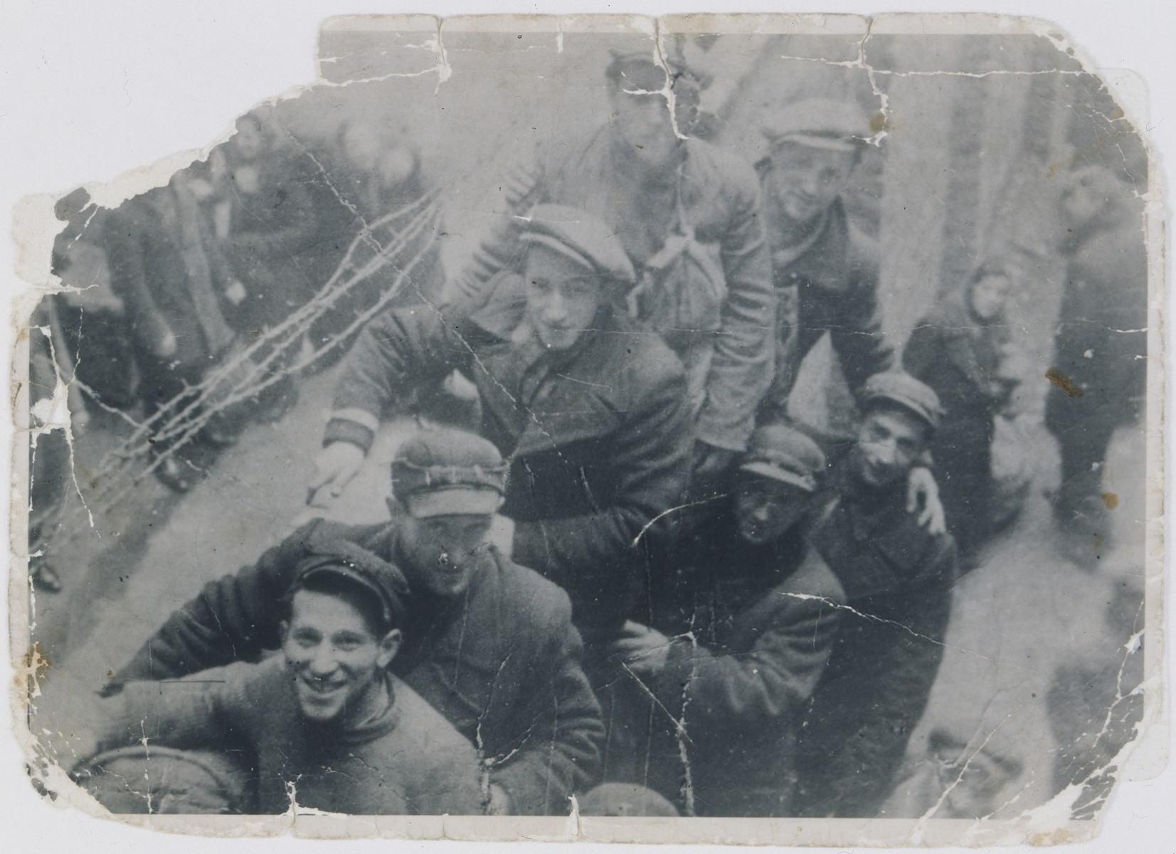 Jewish smugglers pose on a ladder at the top of the Warsaw ghetto wall near Plac Mirowski 9.  Among those pictured is Jakub Wierzbicki (third from the left).