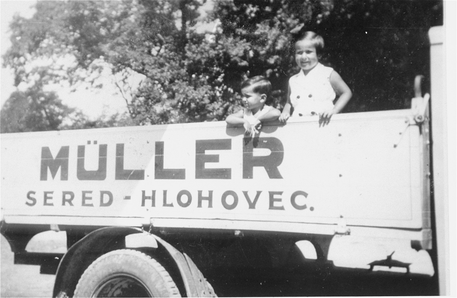 Portrait of the donor's niece and nephew, Agnes and George Muller, standing on the back of a truck bearing the name of their family's firm in Sered, Czechoslovakia.