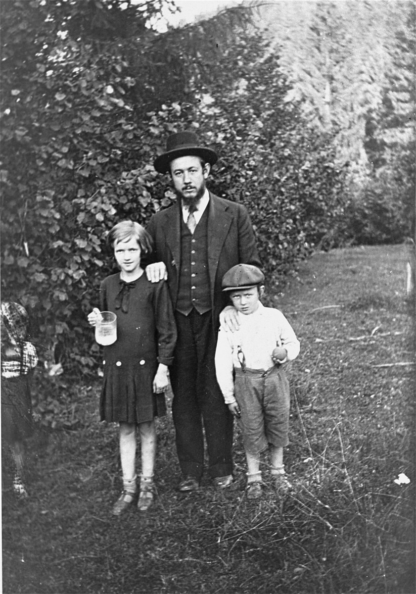 A religious Jewish family poses in a park in Mukachevo.  Pictured are David Grunberger with two of his children, Manci and Nuta Leib.