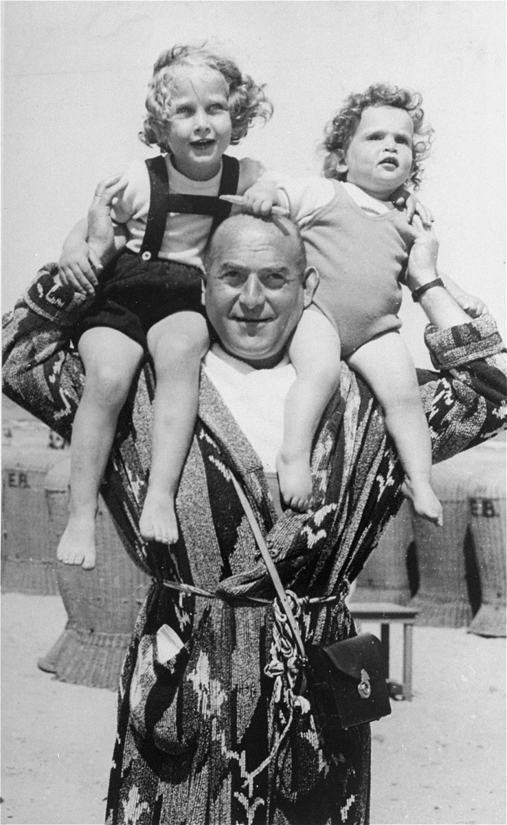Yoka and Francisca Verdoner on their father's shoulders at the beach.