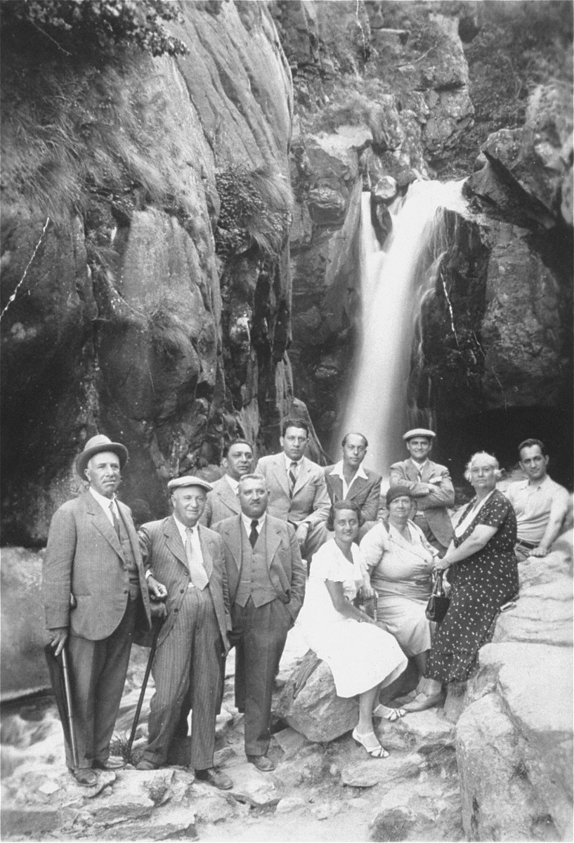 A group of Jewish friends from Sofia pose beneath a waterfall during a hike in the Vitosha Mountains.  Among those pictured is Joseph Yasharoff (back row, far left).