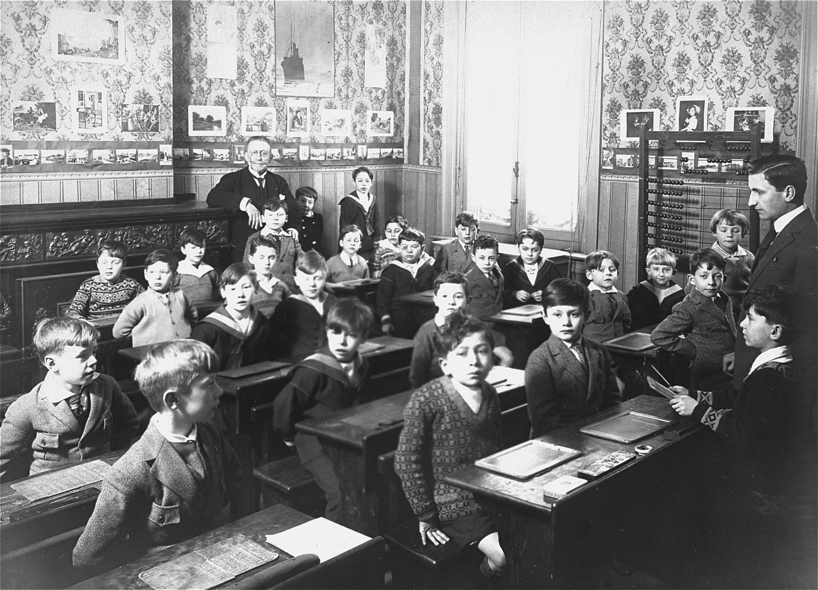 A young boy recites his lessons in a classroom in Antwerp, Belgium.  Among those pictured is Willem Friedman (seated in the middle row, second desk, left side).  Willem was born in 1919 in Holland, but from an early age lived in Belgium.