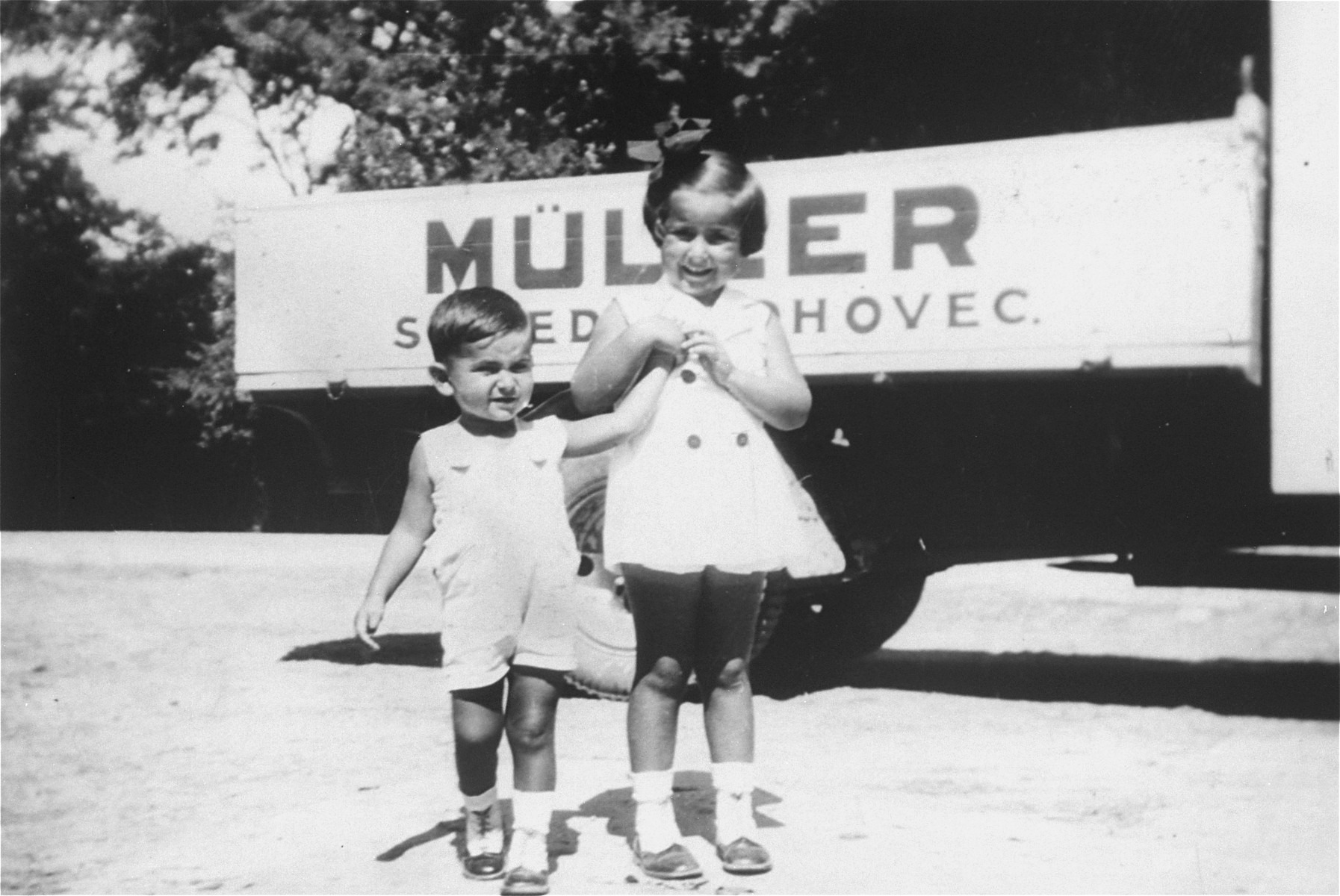 Portrait of the donor's niece and nephew, Agnes and George Muller in front of a truck bearing the name of their family's firm in Sered, Czechoslovakia.