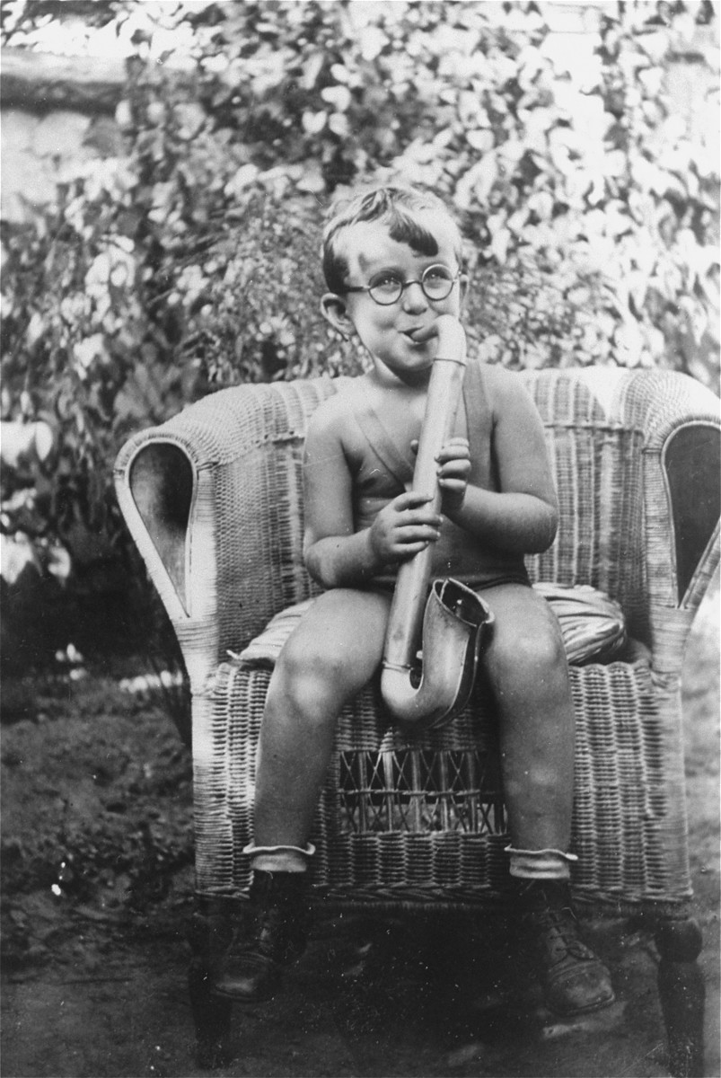 Portrait of the donor's nephew, Gyorgy Szanto, playing a toy saxophone in the garden of his home in Slovensky-Meder, Czechoslovakia.