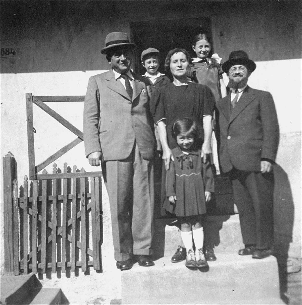 Portrait of the extended Kohn family in Kosice, Slovakia.   Pictured on the bottom step (from left to right) are: Adolph Englander, his sister Marishka Kohn, and her husband.  Marishka's daughter, Gitl Mindl, is standing in front of her.  Standing behind in the back row are Pinchas and his older sister, Dvora Bluma.  Pinchas Kohn was the son of Maryshka (Englander) Kohn and the cousin of donor Doreen Koretz.  The Kohn family was deported to Auschwitz in the spring of 1944 and killed on arrival.  Adolph and Ettela Englander, together with their two children, Ali and Magda, were also deported to Auschwitz in 1944.  Only Magda survived.