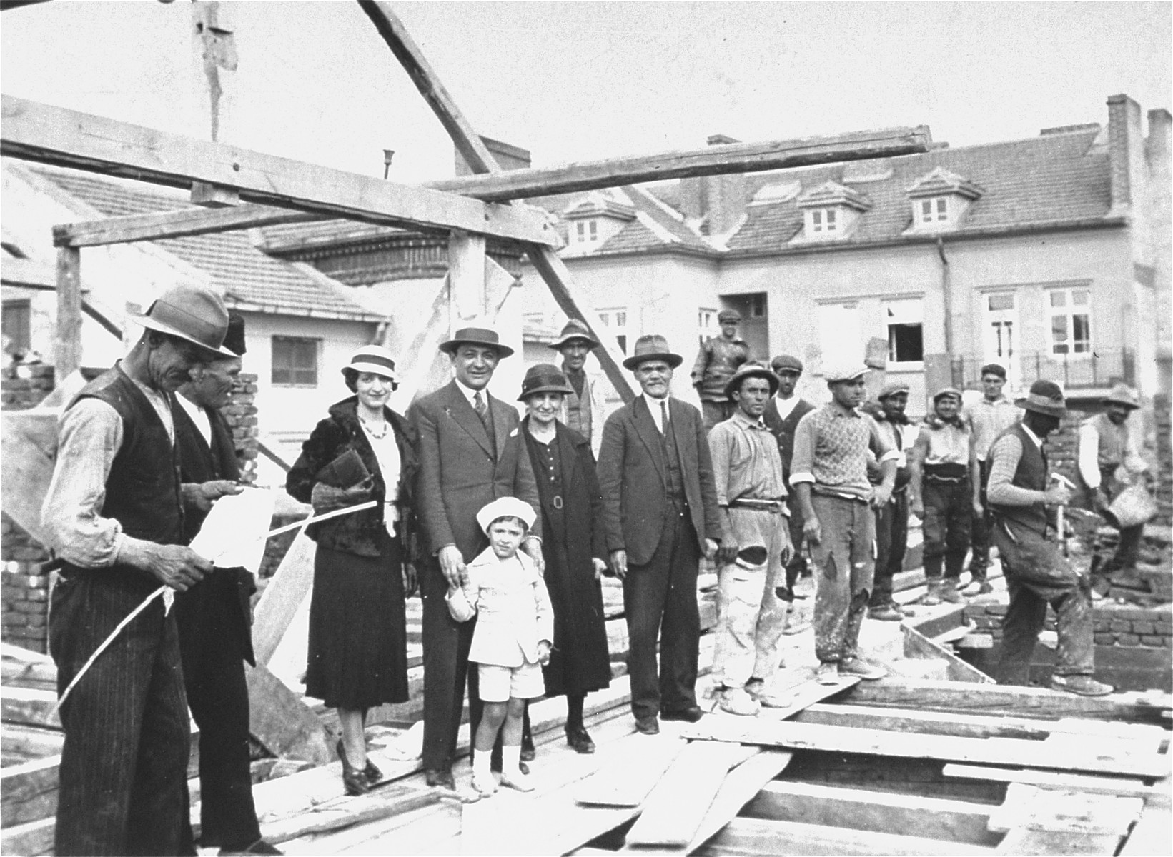 Members of the Yasharoff family pose with construction workers at the site of their new home, a three-story apartment building located at 24 Benkovska Street in Sofia.  Pictured from left to right are: two construction workers, Nelly and Joseph Yasharoff with two-year-old Norbert, Oro and Nissim Yasharoff.