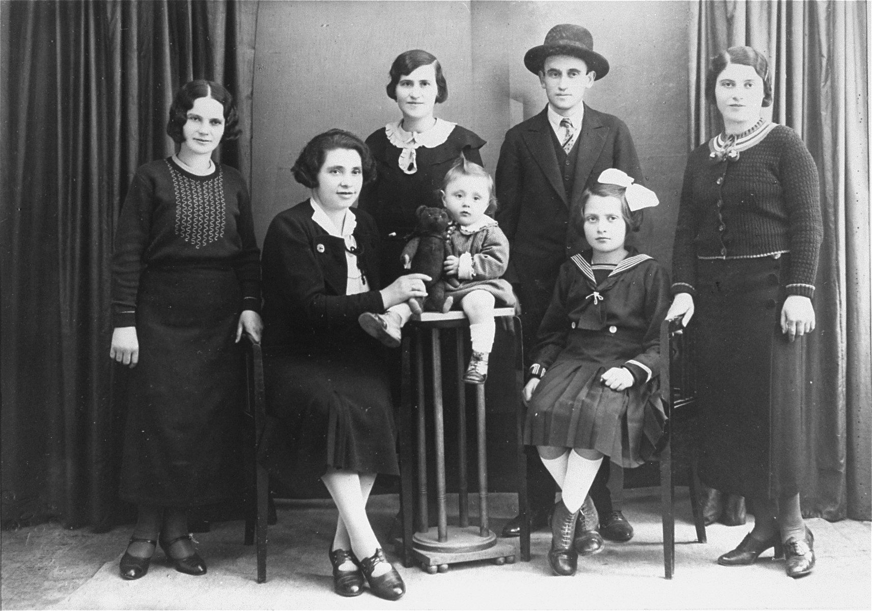 Studio portrait of the Englander family, taken on the eve of Lillian's emigration to the U.S.    Pictured (from left to right) are: Rozi, Ettela (Adolph's wife), Anush (standing), Ali, (Adolph's youngest son); Magda (Adolph's daughter), Shlomi (standing) and Lillian Englander.    Shlomi Englander died soon after this portrait was taken.  Rozi went into hiding with her niece, Magda.  She was caught in 1942 and deported to Poland.  Anush was killed in 1942, along with her husband and child.  Adolph and Ettela Englander, together with their two children, Ali and Magda, were deported to Auschwitz in 1944.  Only Magda survived.
