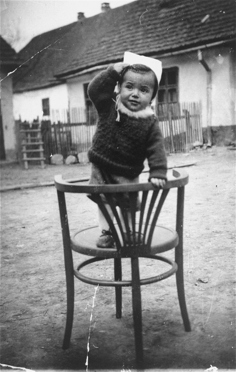 Portrait of a Jewish child standing outside on a chair.  Pictured is Chaim Hersh Kirschenbaum, son of Hanna and Ignatz Kirschenbaum.  Both he and his mother perished in Auschwitz.