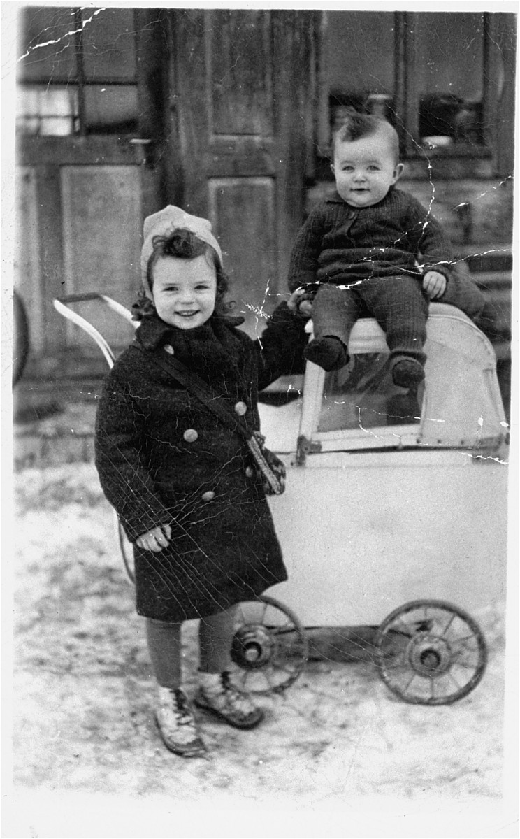 Two young children play outside next to a baby carriage in Bogdan, Transcarpathia.  In 1944, the children and their mother were deported from Bogdan to Auschwitz, where they all perished.  The father, Aharon Sendel, escaped from a labor camp, joined a partisan group and after the war immigrated to Israel.