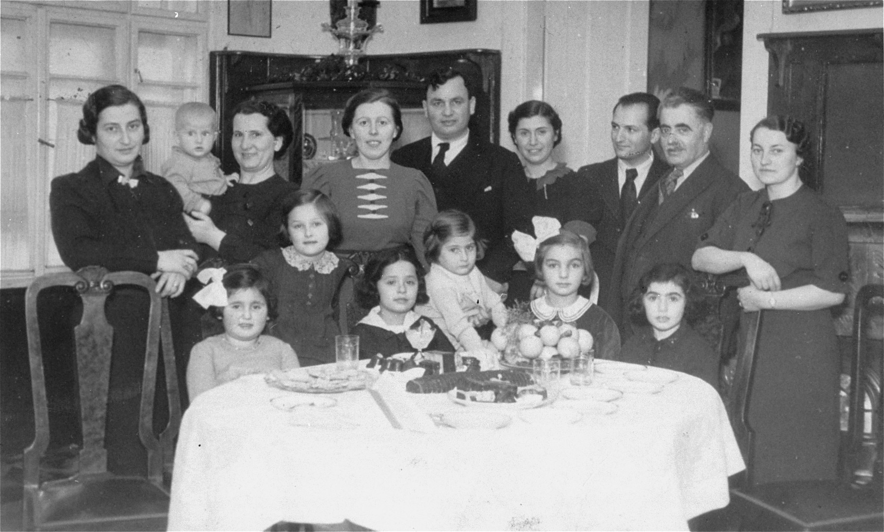 Portrait of the Guth family in their dining room in Lucenec, Czechoslovakia.  Among those pictured are Mano and Klari (Kohn) Guth (fourth and fifth from the right) and Sandor Schonberg, a family friend (second from the right).  The Guths owned an import/export specialties store in Lucenec.  Mano died before the war, while Klari and her two daughters were deported in1944 to Auschwitz, where they perished.