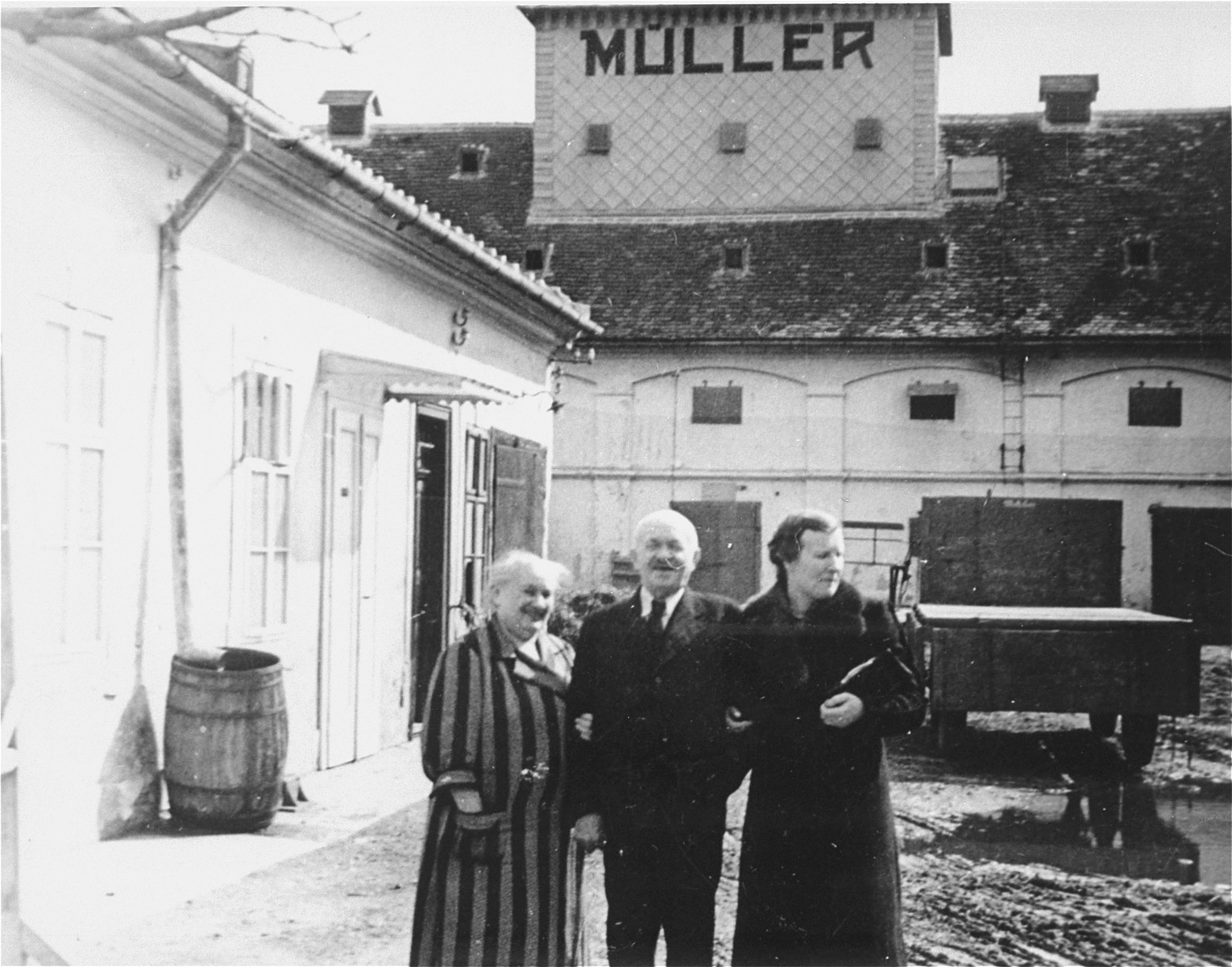 Portrait of the donor's in-laws in the courtyard of the warehouse bearing their name in Sered, Czechoslovakia.  Pictured from left to right are Sophie and Ignac Muller and their daughter-in-law Irene Muller.