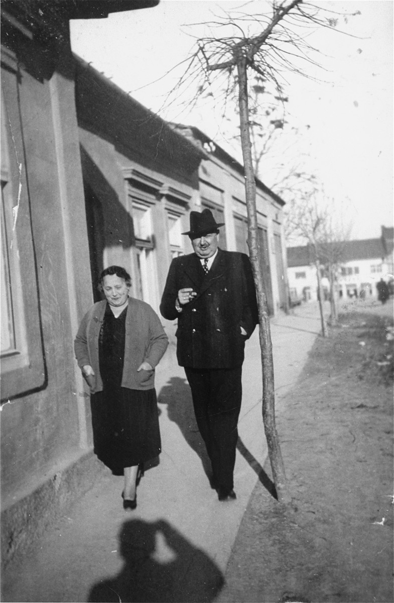 Portrait of the donor's parents, Jakub and Lilly Herzog, walking  along the sidewalk in front of their home in Hlohovec, Czechoslovakia.