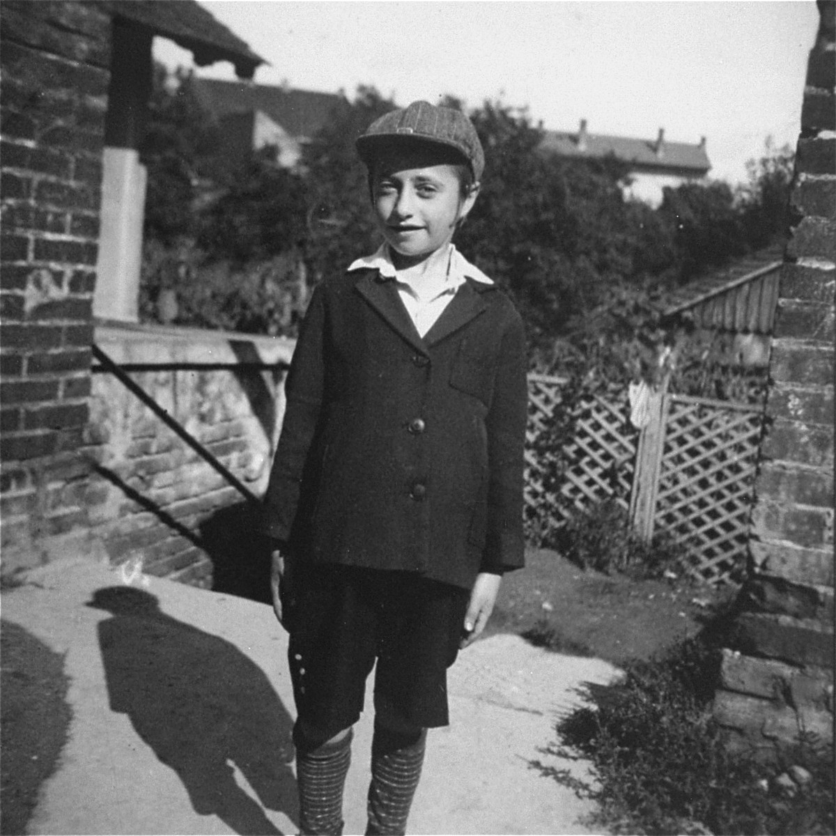 Portrait of a Jewish child standing in a courtyard.  Pictured is Pinchas Kohn.  Pinchas Kohn was the son of Maryshka (Englander) Kohn and the cousin of donor Doreen Koretz.  The Kohn family was deported to Auschwitz in the spring of 1944 and killed on arrival.
