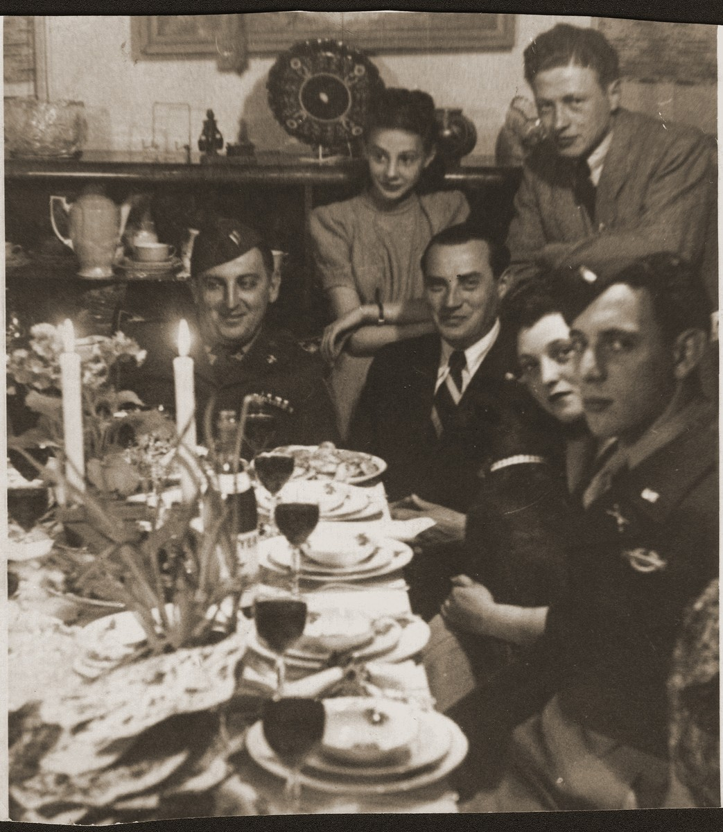 Welek Luksenburg attends a Passover seder in Bayreuth, 1946 at the home of Mary Ganzweich.  Those pictured include Captain Cooly (right), Halinka Merin (back center, daughter of Mary Ganzweich), Welek Luksenburg and Henia Groudaper Shenley.