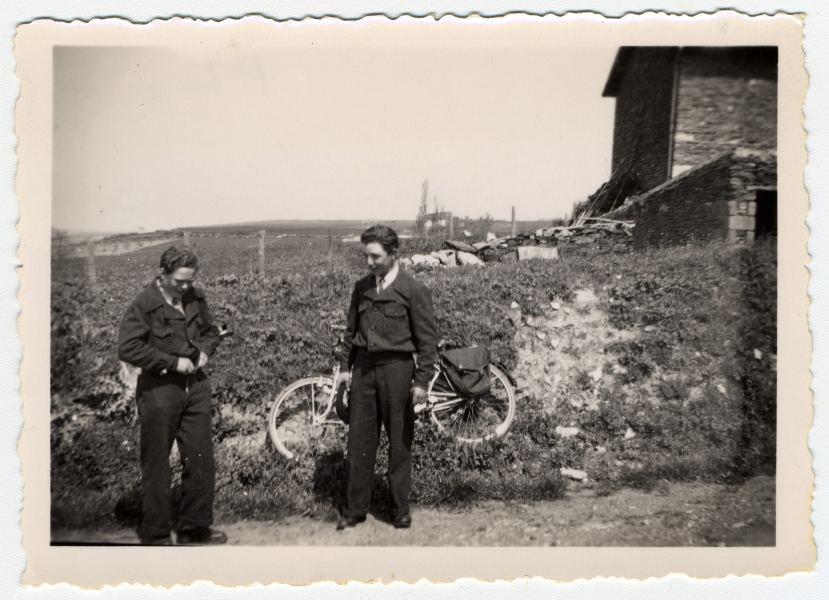 Two Jewish youth in hiding stand in the countryside near Treve.  Pictured on the left is Herbert Karliner.  [On the right is probably Julien Bluchstein.]