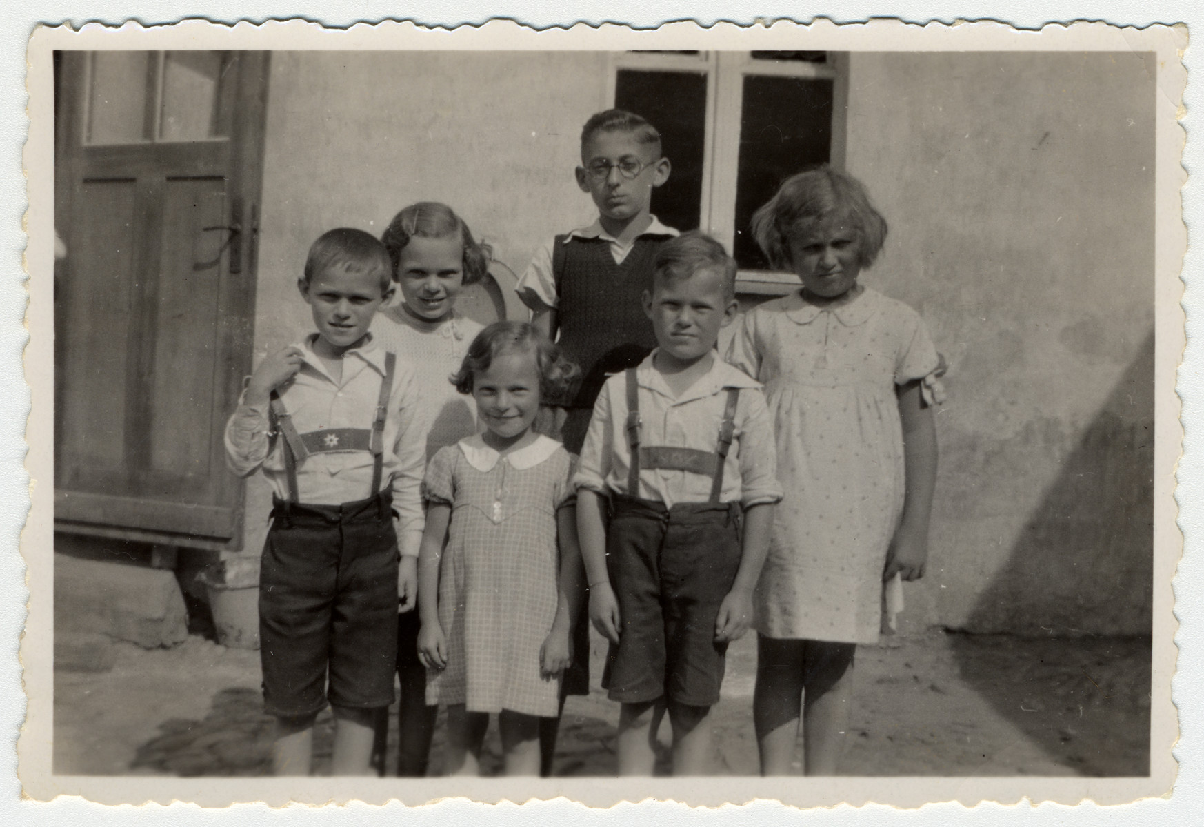Six German-Jewish children pose in front of a building.  Pictured (left to right) are siblings Walter, Ilse, and Ruth Karliner; Horst Scheuer, Herbert Karliner, and Gerda Karliner.