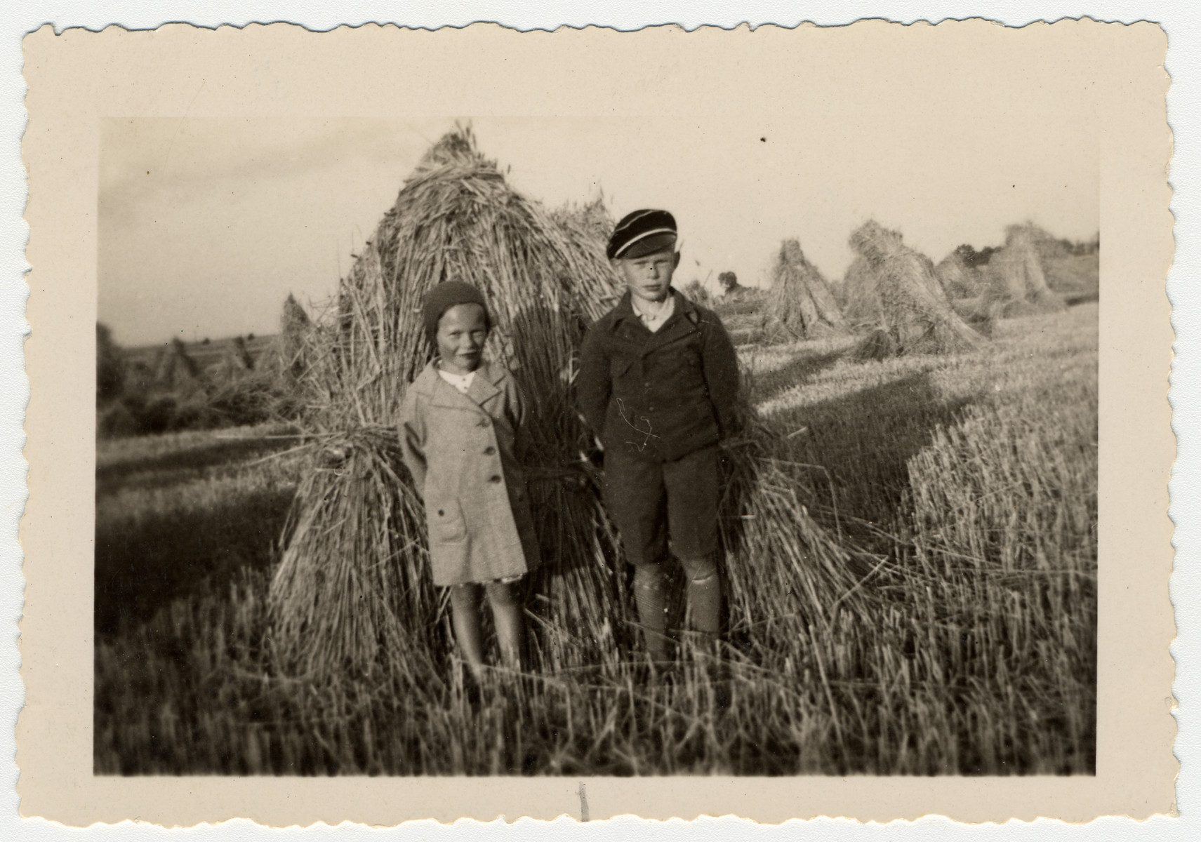 Two Jewish children pose in front of a haystack.  Pictured are Ruth and Herbert Karliner.