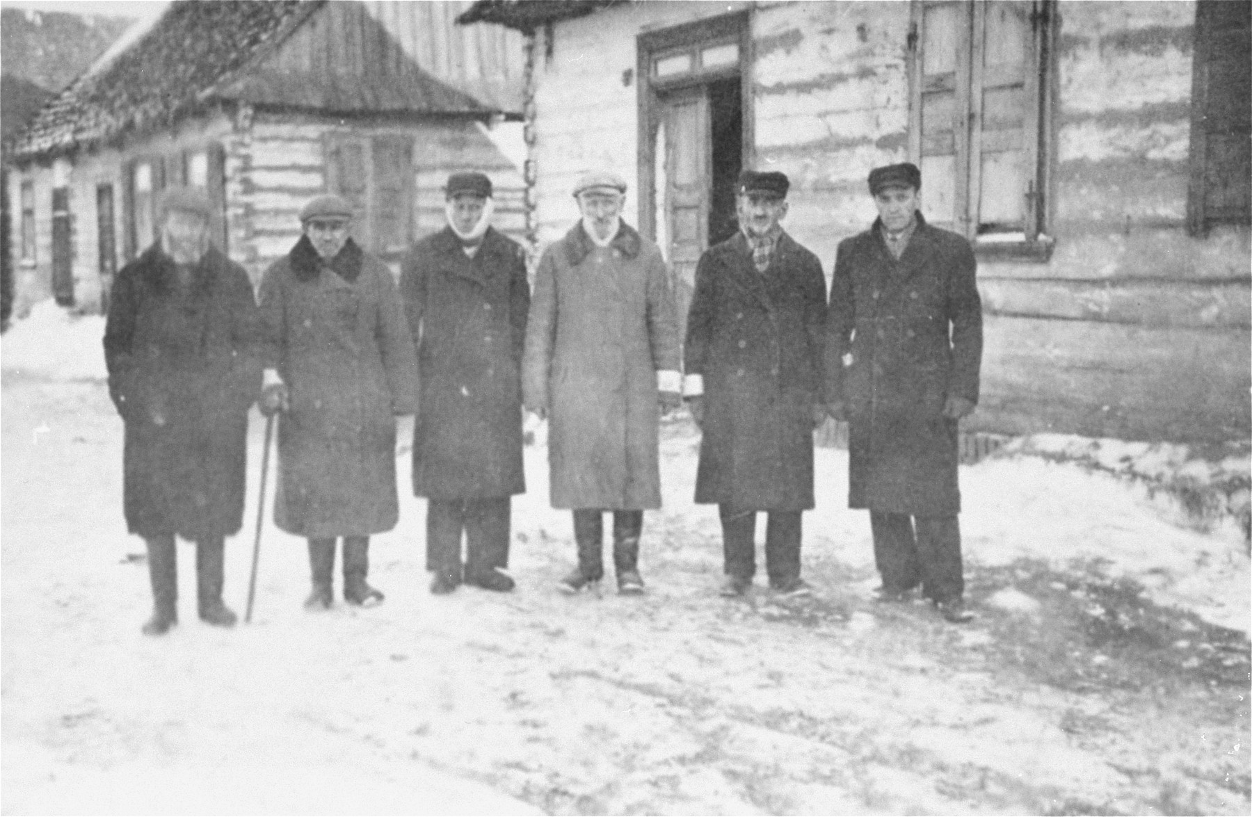 Six members of the local Jewish council pose on a snow covered street in the Wisznice ghetto.