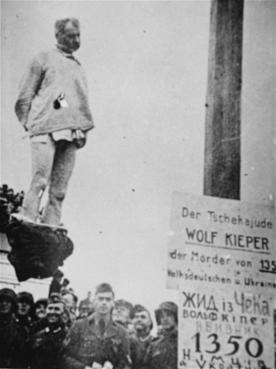 "The hanging of Wolf Kieper on the market square in Zhitomir.    The sign next to him in Ukrainian and German reads ""The Cheka (Soviet secret police) Jew, murderer of 1,350 ethnic Germans and Ukrainians."""