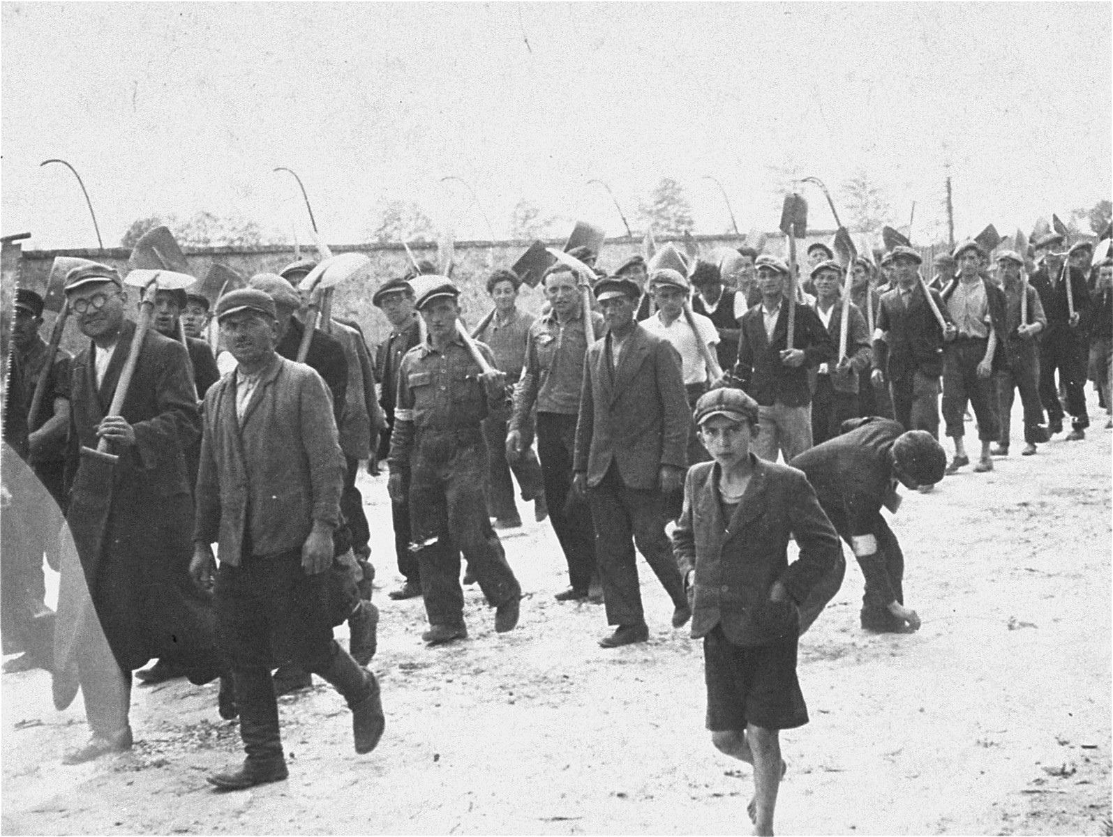 A group of Jewish men and youth from Zarki march to a forced labor site carrying shovels.