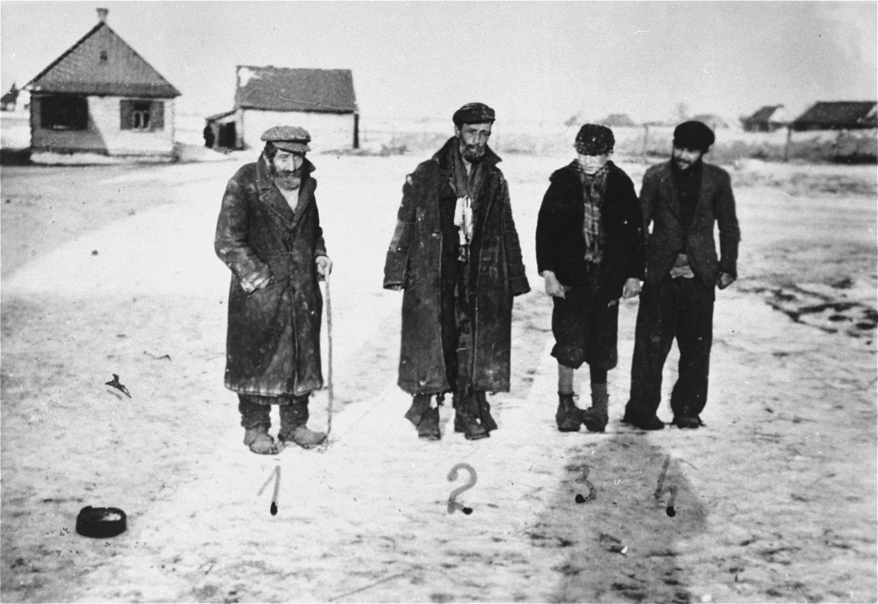 Four Jewish men pose on an unpaved road in the Wisznice ghetto.  Pictured from left to right are: Jeko Frydman, Zachary Bajmdzole, Pinkus Rozenberg and Moszko Kaszemadzer.