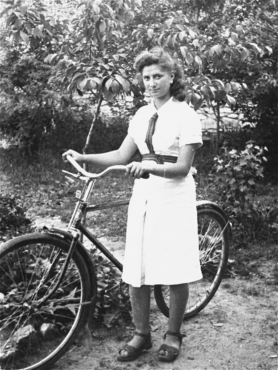 Lodzia Hamersztajn poses holding a bicycle at the Hashomer Hatzair Zionist collective in Zarki.