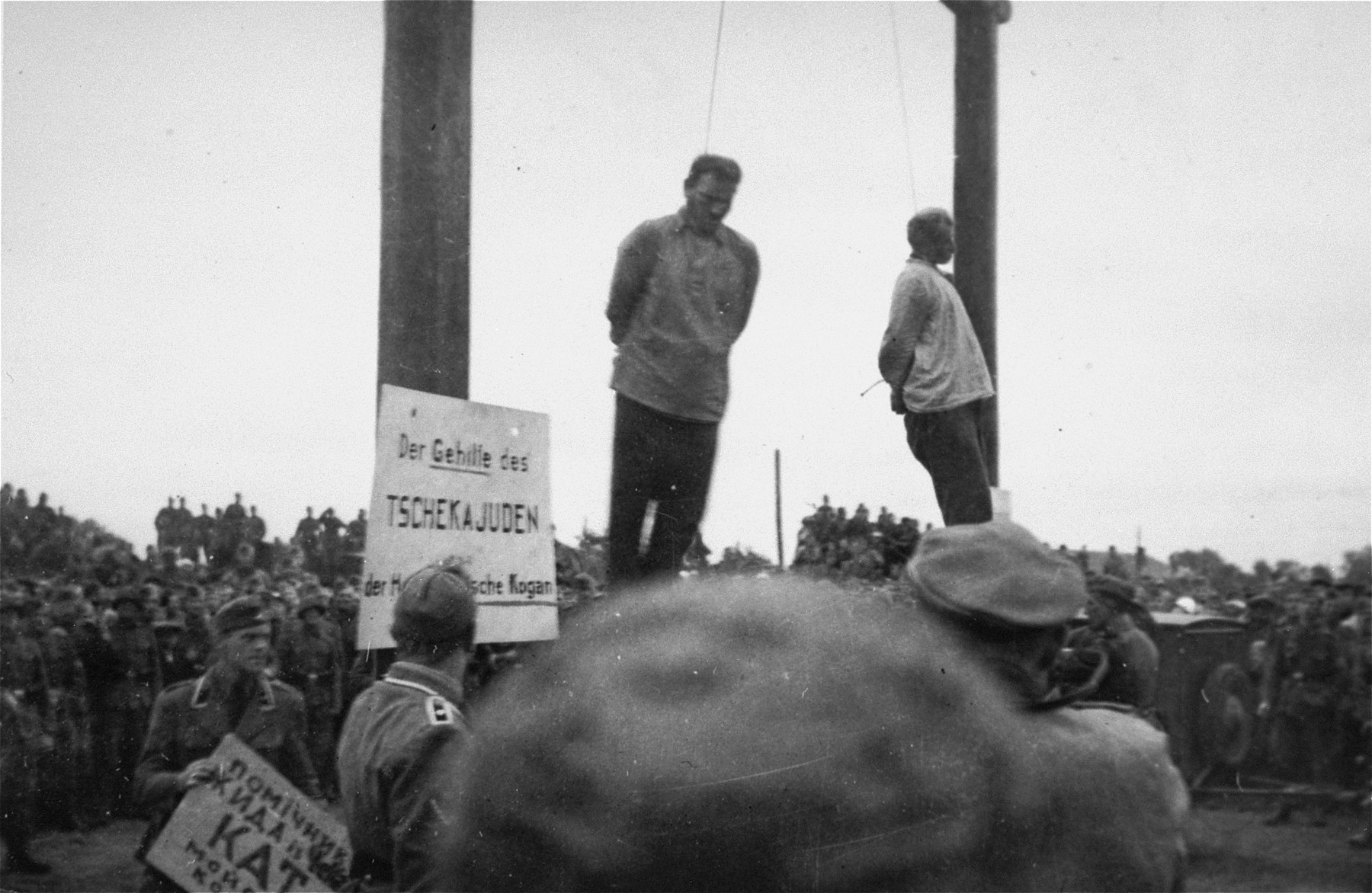 "The hanging of Mosche Kogan (left) and Wolf Kieper on the market square in Zhitomir.    An SD officer is tacking up signs in Ukrainian and German that read ""The assistant of the Cheka (Soviet secret police) Jew, the hangman Mosche Kogan."""