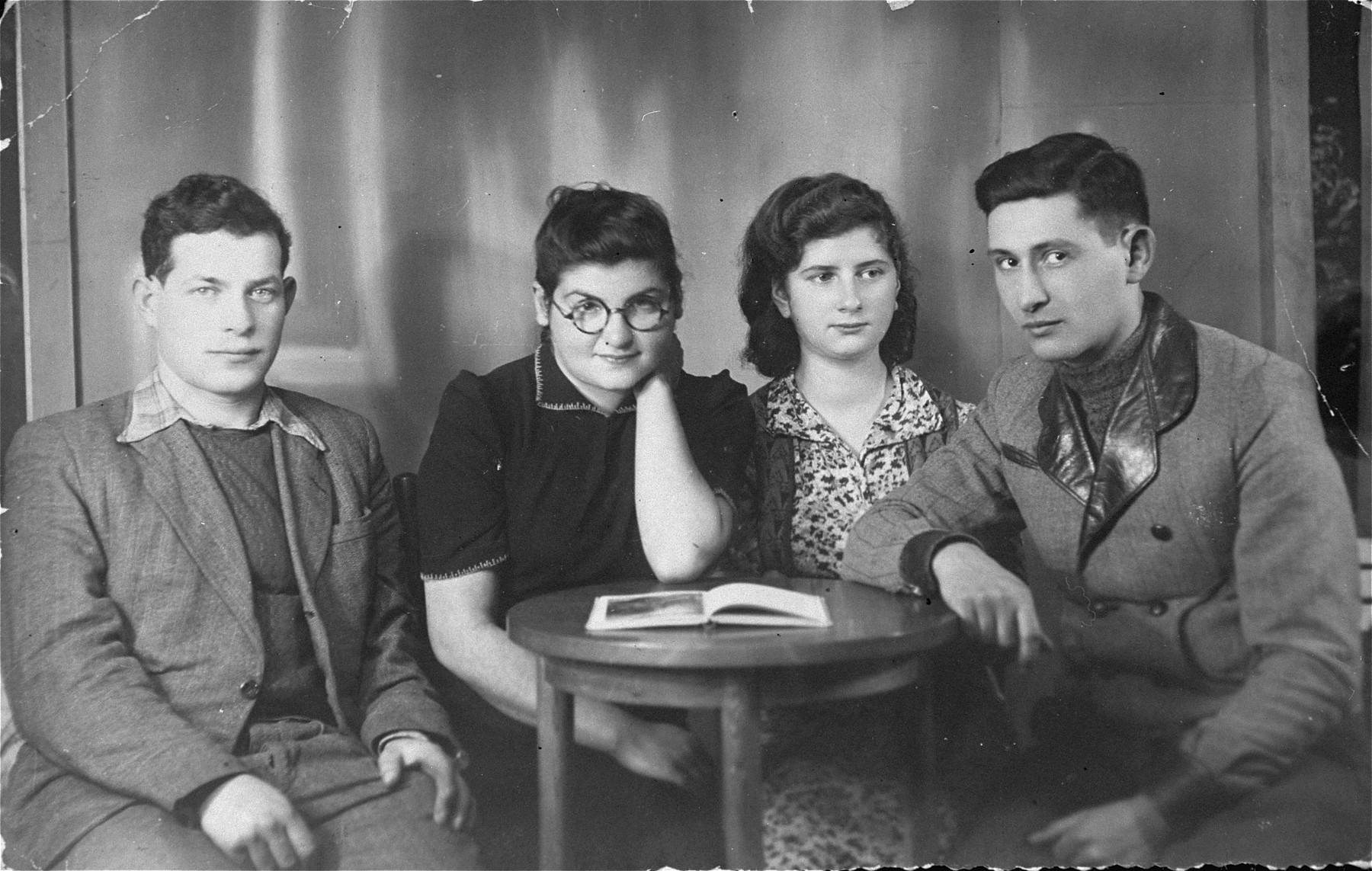 Four members of the Hashomer Hatzair Zionist collective in Zarki are seated around a table.  Pictured from left to right are: Aron Szwarc, Tamar (last name unknown), Lodzia Hamersztajn, and Berel Lemel.
