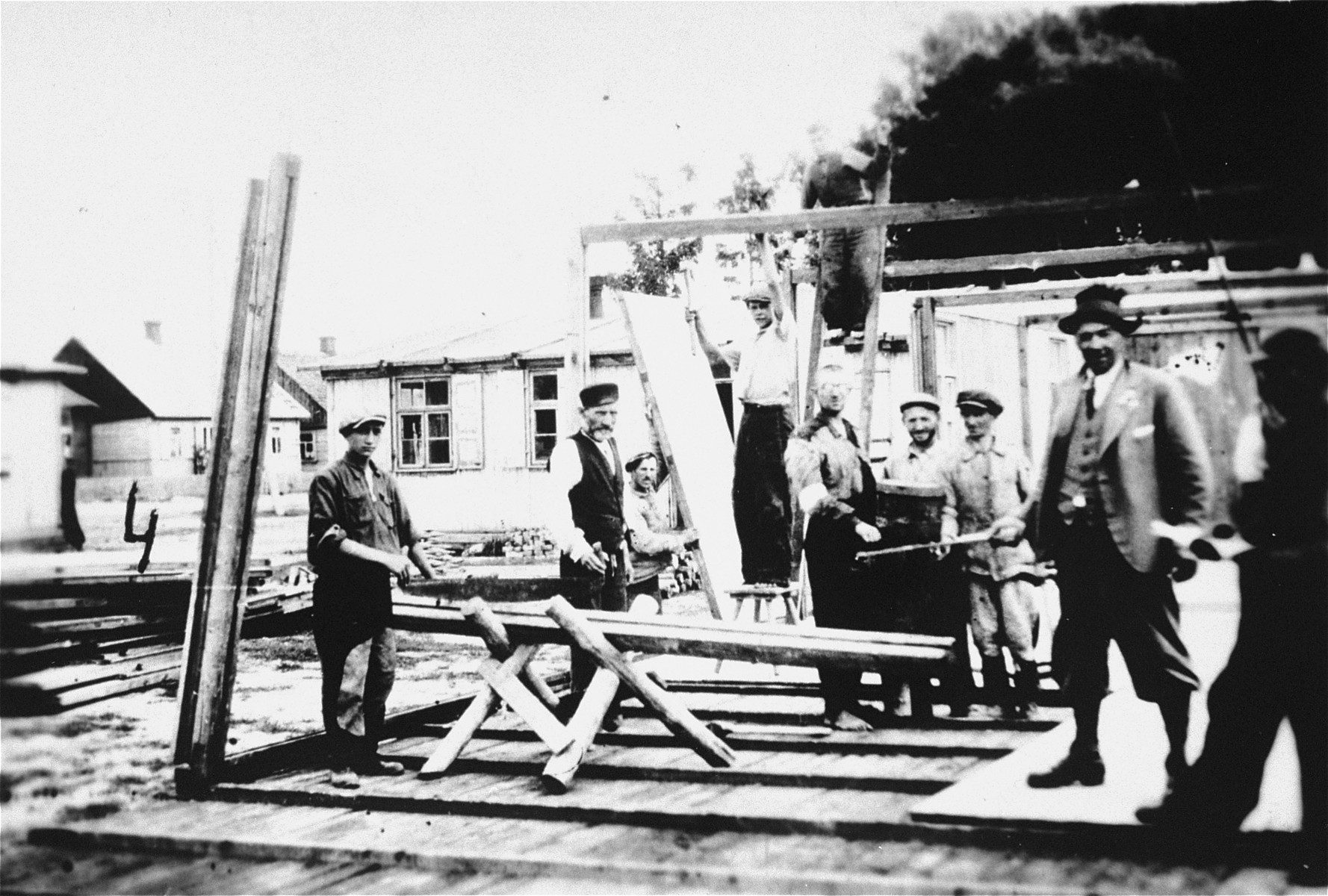 Jewish forced laborers from the Wisznice ghetto assist a Polish carpenter in the construction of new barracks.  Standing on the stool is Kazimierz Szubarczyk, a Polish carpenter.  A German overseer stands at the right holding a stick that he often used to beat Jews.