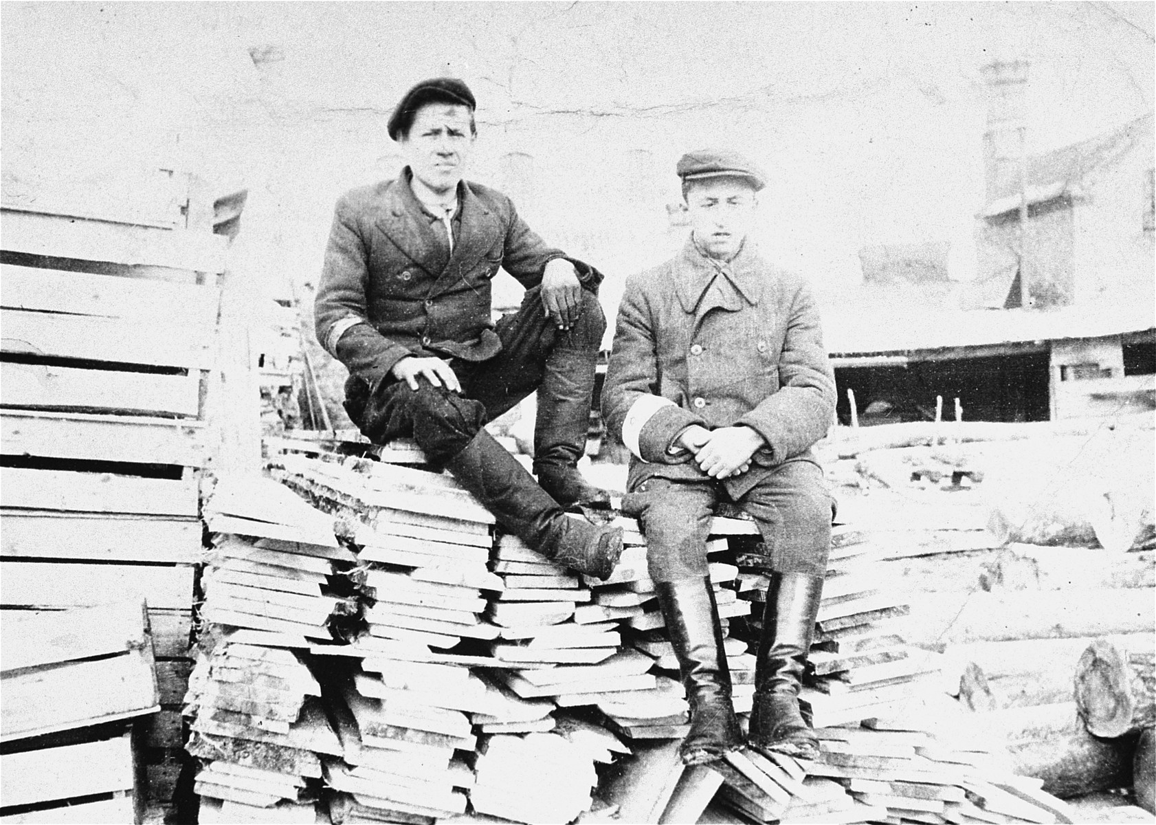 Isaac Ejber and Jacob Rajs sit on a wood pile at a sawmill near the Wlodawa ghetto.  Both were resistance fighters who were killed by the Germans in Adampol.