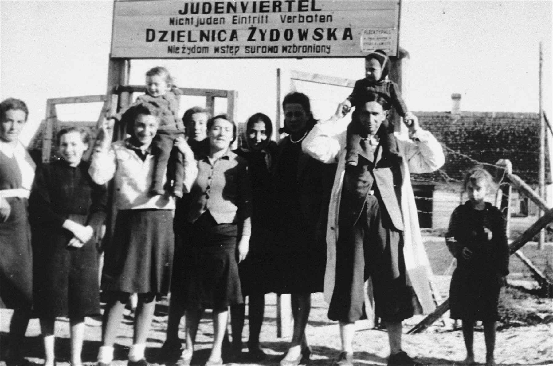 """A group of Jews pose in front of the entrance to the Wisznice ghetto.  The sign above the gate, which is written in German and Polish, reads: """"Jewish quarter, entrance to non-Jews is forbidden."""""""