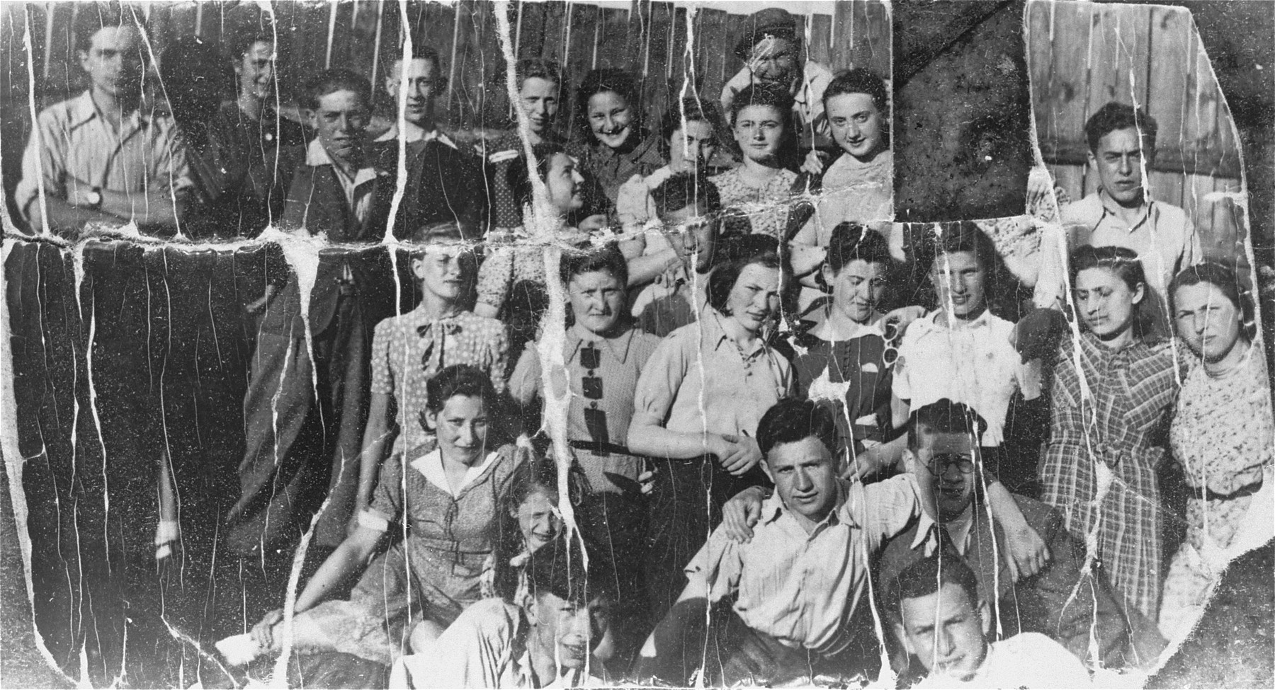 Group portrait of members of the Akiva Zionist youth movement in Tomaszow Mazowiecki.   The portrait is taken in the yard of Akiva's headquarters on Kryzowa Street.  Pictured from right to left: (top row) unknown, Lonia Lisopraska (cut out), Reginka Orenbach, Motek Kuper (above), Stefa Wygocka, Bronka Plat, Tuska Fuks, unknown, unknown, Halinka Rubinek, Mula Weisman.  Also pictured are Icek Rosenblat (leader of the group), Bronka Rozen, Jadzia Strykowska, Jurek Wald, Chajka Rozenbaum, Aronek Cohen, Lolek Donner.  The donor, Judy Lachman, is the girl directly below the hole. She carried the photo with her throughout the war.