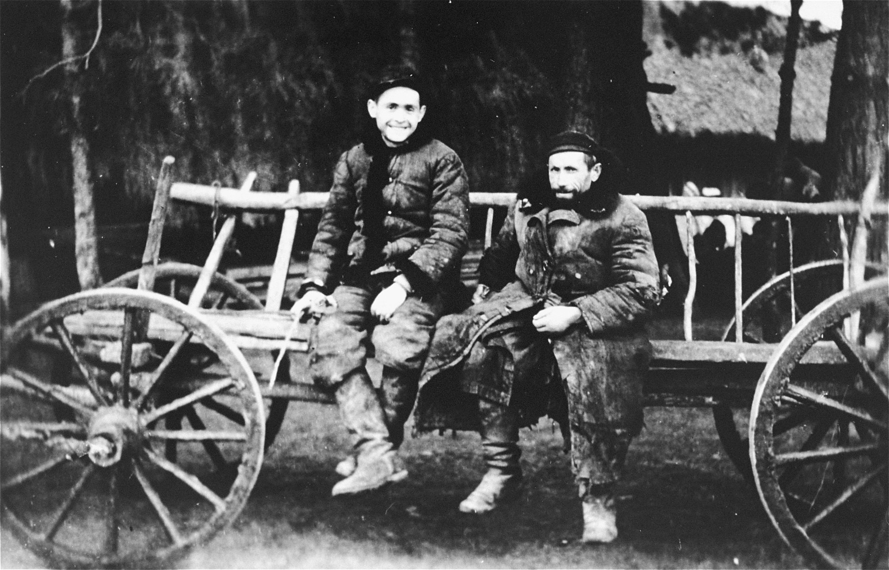 A father and son sit on a wagon in the Wisznice ghetto.